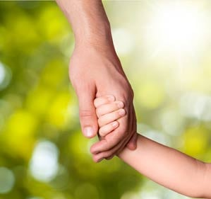 Picture of parent handing the hand of a child